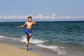 Boy on summer holidays running the sea beach Royalty Free Stock Photos