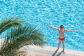Boy sunbathe on the edge of the pool near palm leaf and raised his hands Stock Images