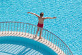 Boy sunbathing on the edge of the pool raised his hands up Stock Photos
