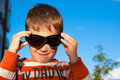 Boy in sunglasses smiling outdoors Royalty Free Stock Images