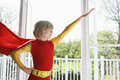 Boy in superhero costume with arm extended young indoors Royalty Free Stock Photos