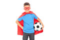 Boy in superhero costume holding a football isolated on white background Stock Image