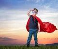 A boy in a Superman costume stands
