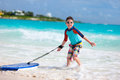 Boy surfing little on vacation having fun on boogie board Stock Photos