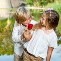 Boy surprising girl with flower portrait of cute girlfriend red rose at lakeside Stock Photo
