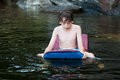 Boy swiming in a lake young playing with boogie board Royalty Free Stock Image