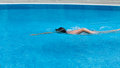A boy is swimming in a pool side view the breaststroke an outdoor Royalty Free Stock Photo