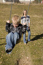 Boy in swing and mother behind Stock Photography