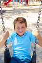 Boy On Swing In Park Royalty Free Stock Photo
