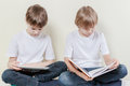 Boy with tablet computer and kid reading a book. Kids education leisure concept. Royalty Free Stock Photo