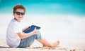 Boy with tablet device at beach little playing on a Royalty Free Stock Photography