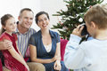 Boy taking photo of family by christmas tree young sitter mother and father Stock Image