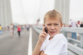 Boy talking on mobile phone golden bridge during a holiday in vladivostok Royalty Free Stock Images