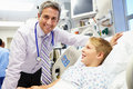 Boy talking to male consultant in emergency room looking at camera smiling Royalty Free Stock Photography