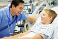 Boy talking to male nurse in emergency room looking at each other smiling Stock Images