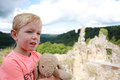 Boy with teddybear a on a ruin staring and enjoying Stock Photo
