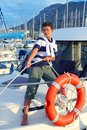 Boy teen sailor mooring boat rope in harbor Royalty Free Stock Image