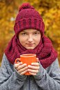 Boy teenager with a cup of tea coffee in a voluminous large cozy scarf and cap of burgundy color Royalty Free Stock Photo