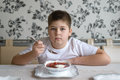 Boy teenager eating soup at  kitchen table Royalty Free Stock Photo