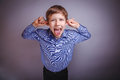 Boy teenager european appearance brown grimaces a experiencing joy Royalty Free Stock Photos