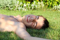 Boy teenager on the grass smiling lying Stock Images