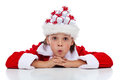 Boy thinking of his christmas presents wearing a santa hat full tiny gift boxes Royalty Free Stock Photography