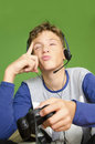 Boy thinking next move video games teenage playing with headphones on his head trying to figure out holding joystick in his hand Royalty Free Stock Photo
