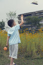 Boy throw hat chinese into air in garden Royalty Free Stock Photo