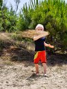 Boy throwing sand young in front of a dune rotation Royalty Free Stock Images