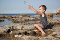 Boy throws stones into the sea Royalty Free Stock Photo