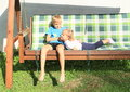 Boy tickling girl on a wooden swing young swinging and Stock Photos