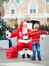 Boy about to embrace santa claus rear view of in courtyard Stock Images