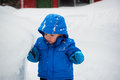 Boy touching a deep snowbank on snowy day little is standing next to which is as tall as he is he is the with his Royalty Free Stock Photo