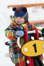 Boy on toy motorcycle at playground in winter Royalty Free Stock Image