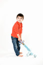 Boy with a toy swan and christmas balls little men standing on floor Royalty Free Stock Image