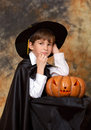 The boy with traditional halloween pumpkin dressed in black raincoat Royalty Free Stock Photo