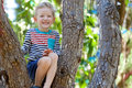 Boy at the tree excited adorable sitting branch of Royalty Free Stock Photo