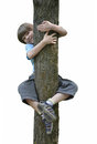 Boy in a tree the threw his arms around trunk and legs hanging on him and smiling Stock Photography