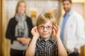 Boy trying glasses with optometrist and mother at portrait of smiling standing in background store Royalty Free Stock Image