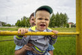 Boy is trying to catch up on the bar young father and son years at old stadium in village Royalty Free Stock Images