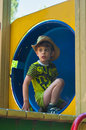 Boy in the tunnel in cowboy hat sits at playground is blue s t shirt light green color he is wearing Stock Photos
