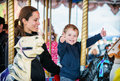 Boy with two thumbs up with mother on carousel a happy and son are riding a together smiling and having fun at an amusement park Stock Photography