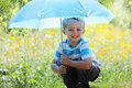 Boy with umbrella rain and sunshine a smiling holding an in a meadow of wildflowers Stock Photos