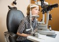 Boy undergoing eye examination with slit lamp little in store Stock Photos