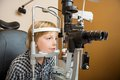 Boy undergoing eye examination with slit lamp preadolescent in store Royalty Free Stock Photography