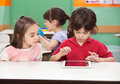 Boy using digital tablet with friend at desk little female in kindergarten Stock Image