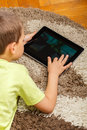 Boy using digital tablet lying on floor and Royalty Free Stock Photos