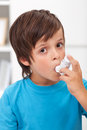 Boy using inhaler for respiratory system issues Stock Image