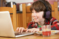 Boy Using Laptop Whilst Eating Breakfast Royalty Free Stock Images