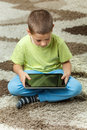 Boy using a tablet sitting on the floor Royalty Free Stock Photo